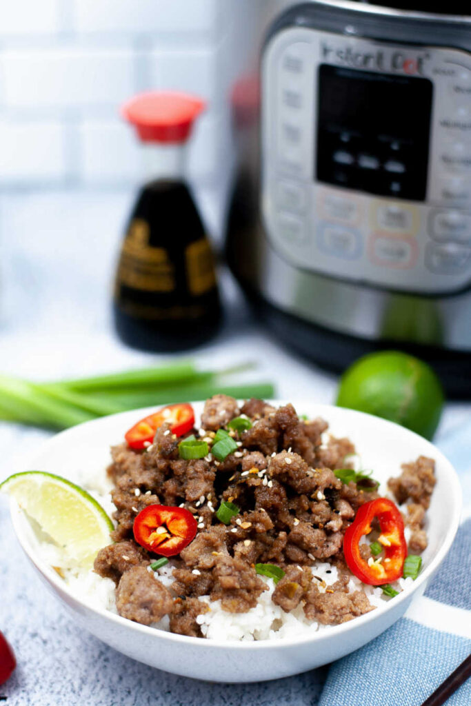 Bowl of caramel pork with lime wedge and jalapenos near pressure cooker.