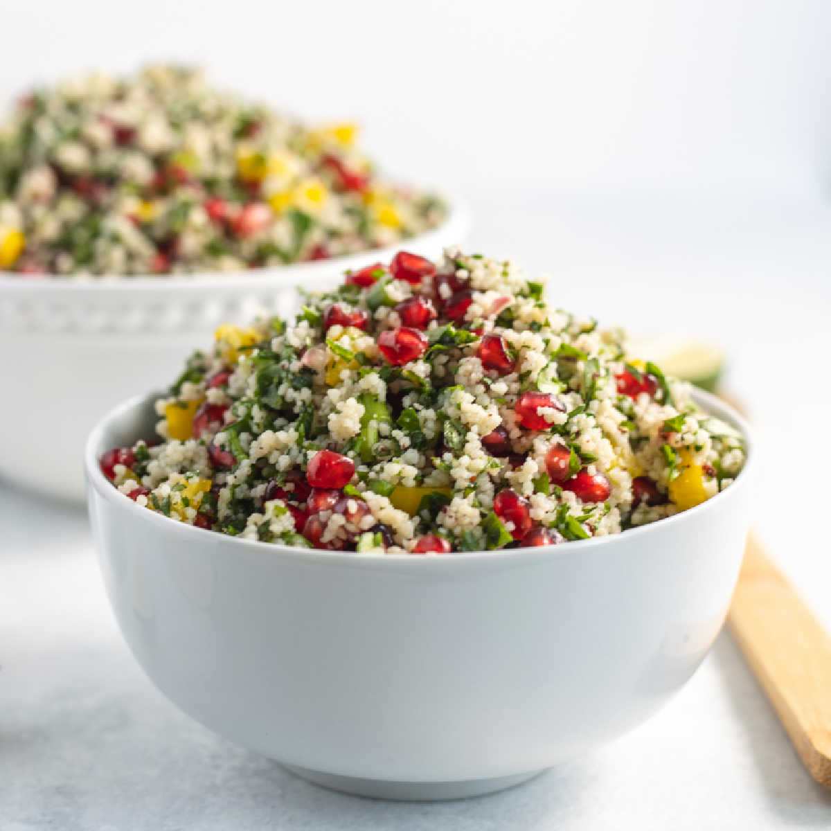 Bowl of pomegranate couscous salad with fresh herbs, bright pomegranate arils and bits of yellow bell pepper, ready to eat.