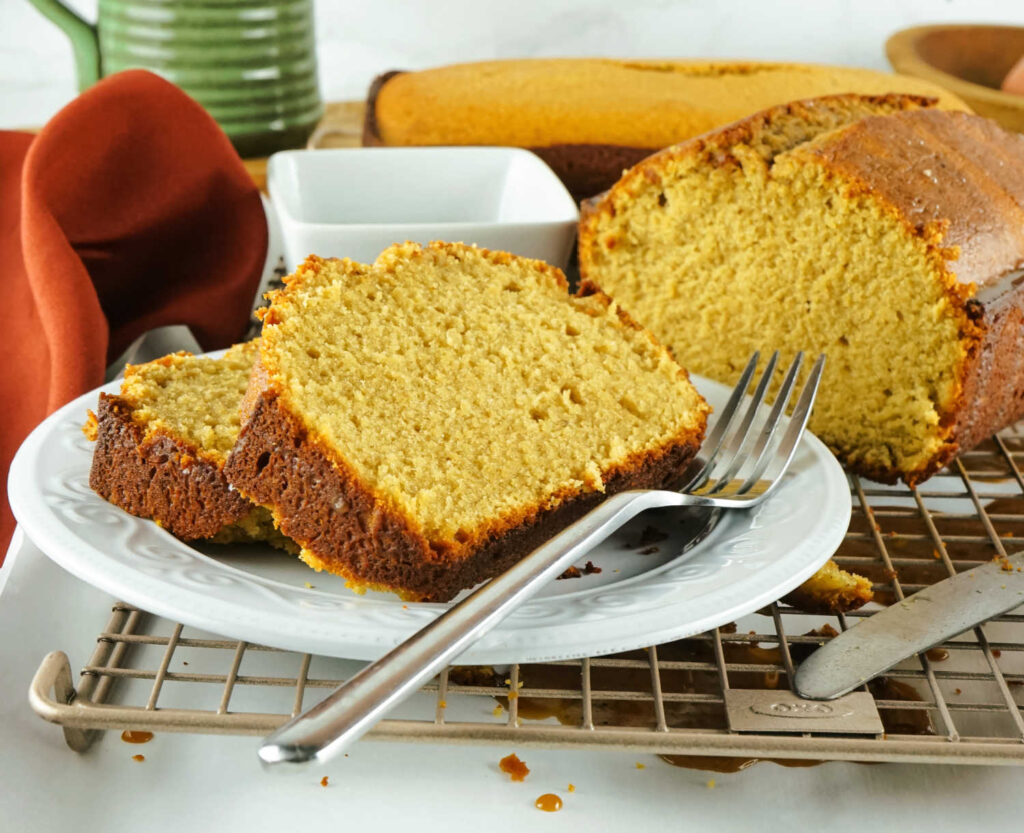 Slices of loaf shaped coffee flavored pound cake on plate with fork.