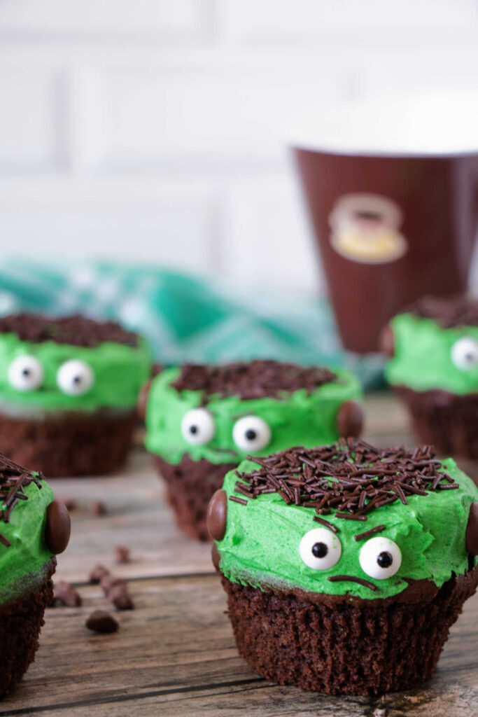 Lots of Frankenstein cupcakes in front of coffee cup.