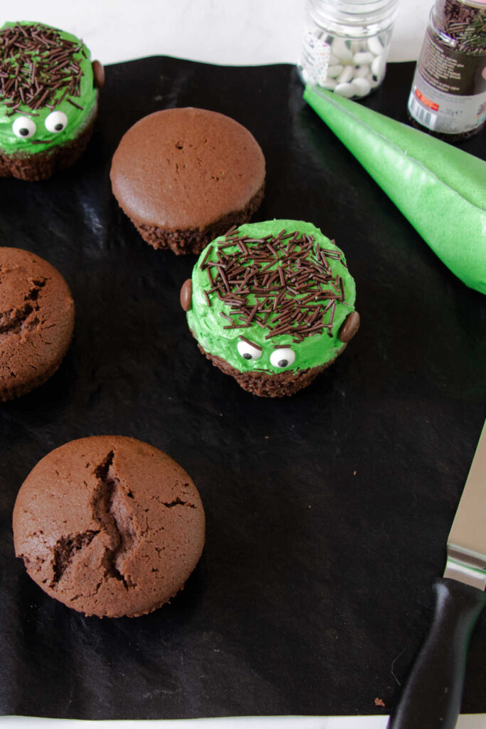 Freshly baked chocolate cupcakes with piping bag filled with green buttercream, small thing candy eyes and chocolate sprinkles.