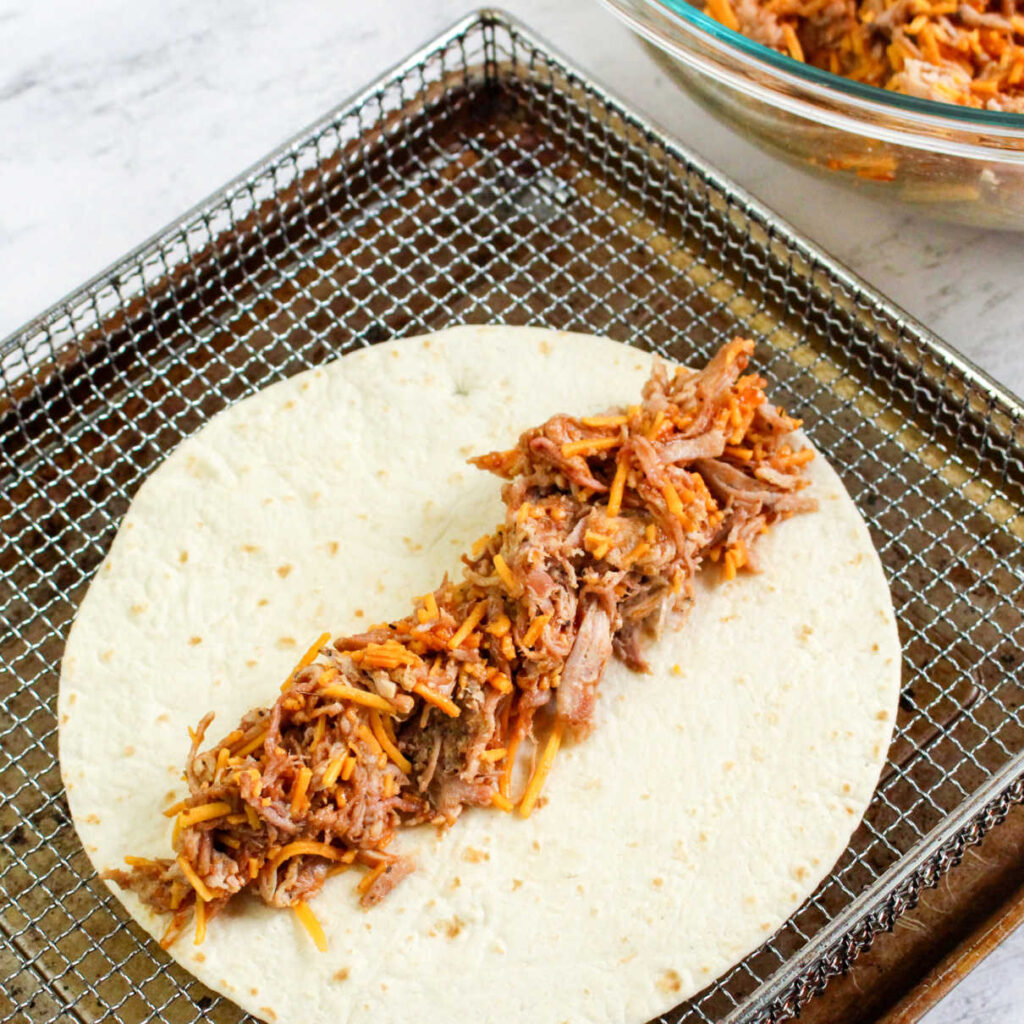 tortilla with bbq pulled pork on it ready to be rolled into flauta and put into air fryer.