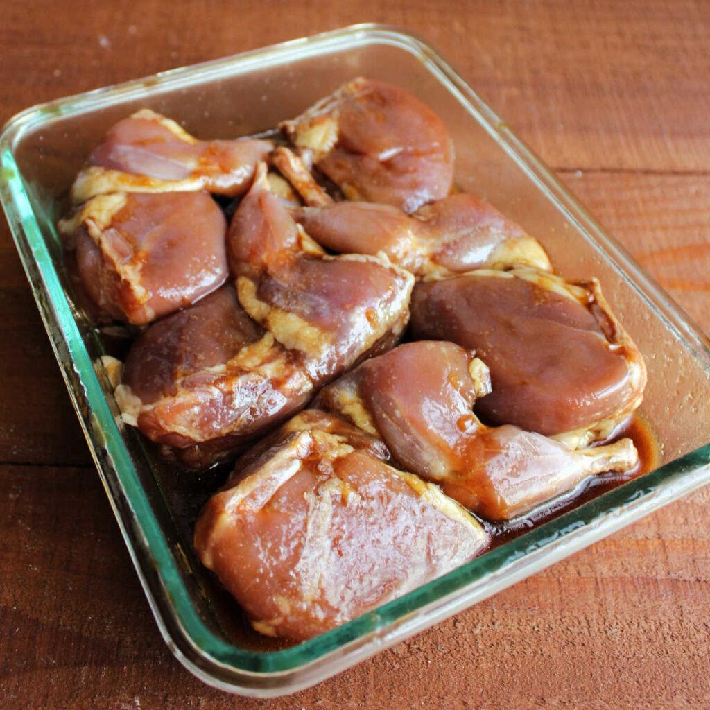 Quail soaking in soy sauce and brown sugar marinade mixture.