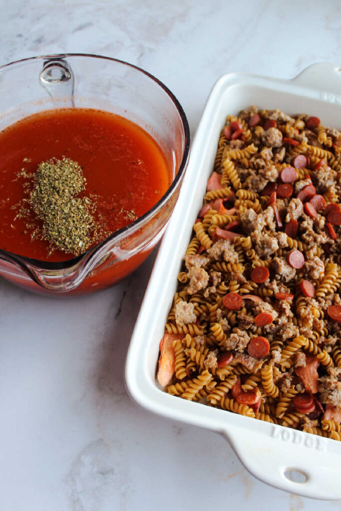 Pan of pasta topped with sausage and pepperoni next to bowl of sauce with oregano and garlic.