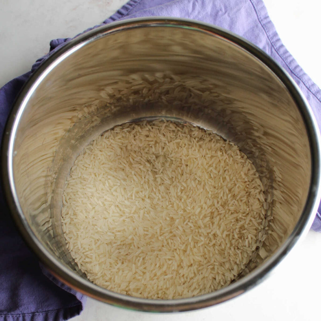 Raw long grain white rice in instant pot, ready to be made into pudding.