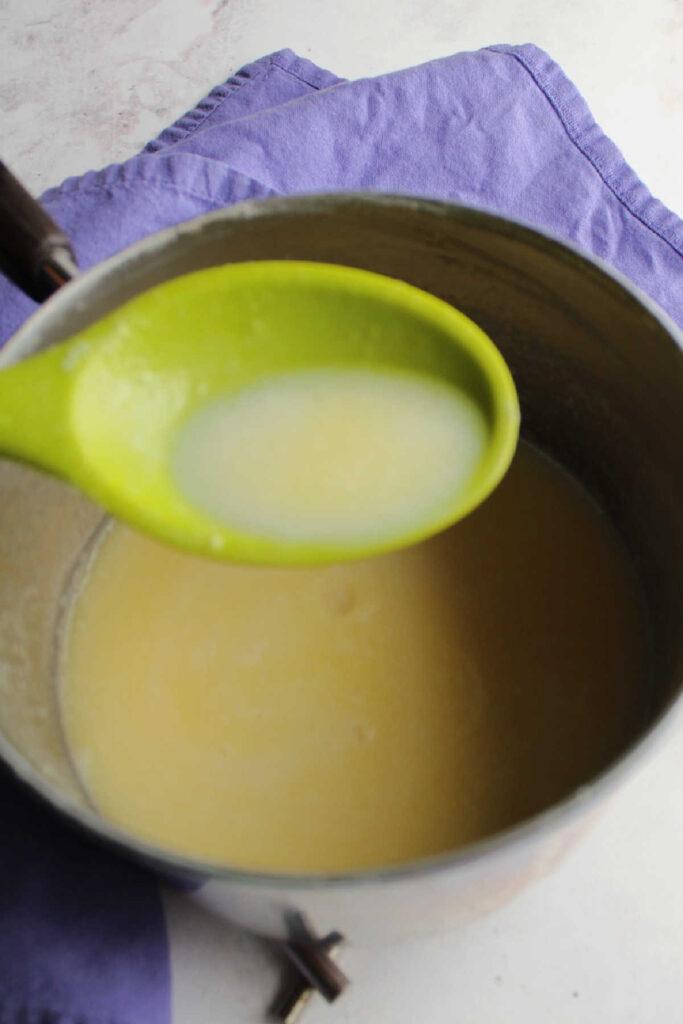 Spoonful of hot sweetened condensed milk over saucepan.