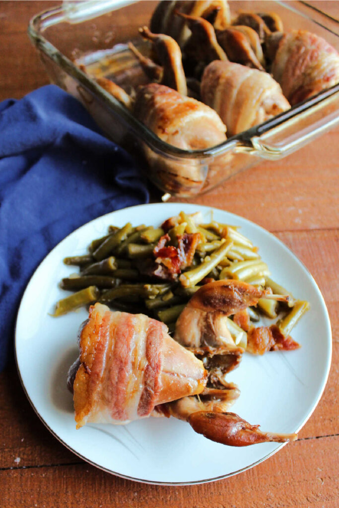 Quail and green beans on plate with pan full of quail in background.