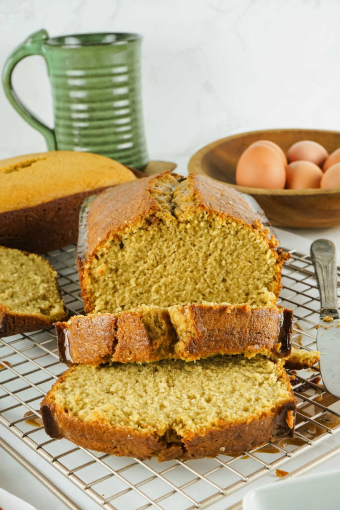 Tan coffee flavored pound cake loaf on wire rack with a few thick slices cut.