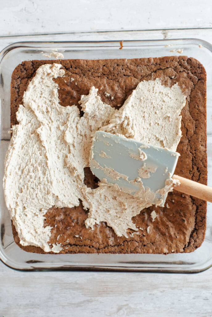 Spatula smoothing a little bit of coffee buttercream over cooled brownies.