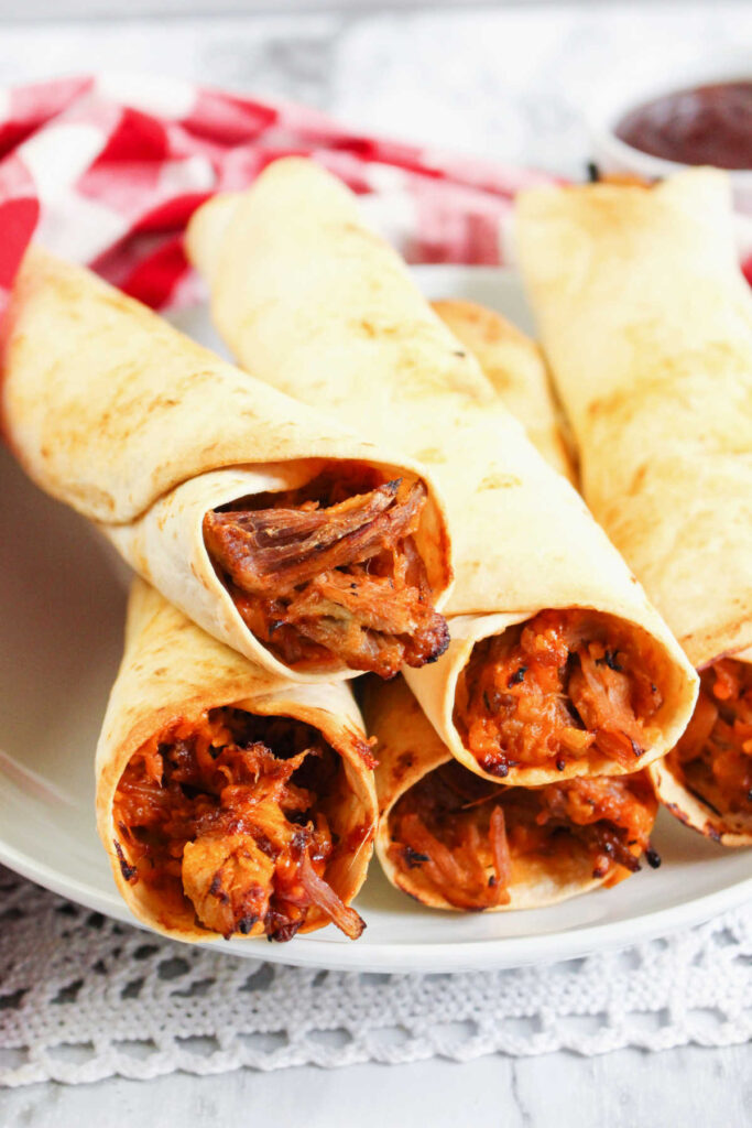 Plate of air fried pulled pork flautas ready to eat.
