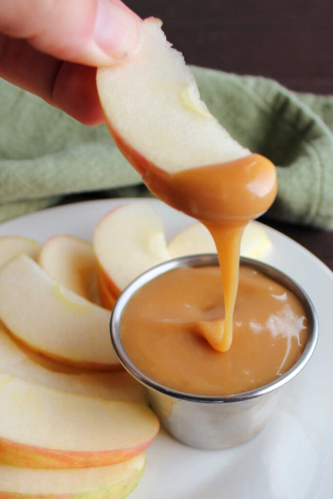 Apple slice with thick caramel dip dripping off it.