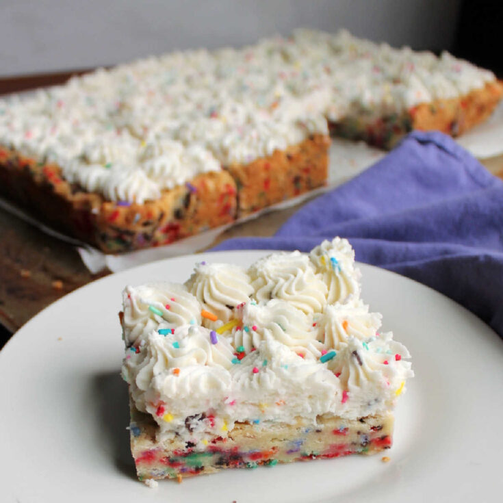Funfetti sugar cookie bar with swirls of frosting on plate ready to eat.
