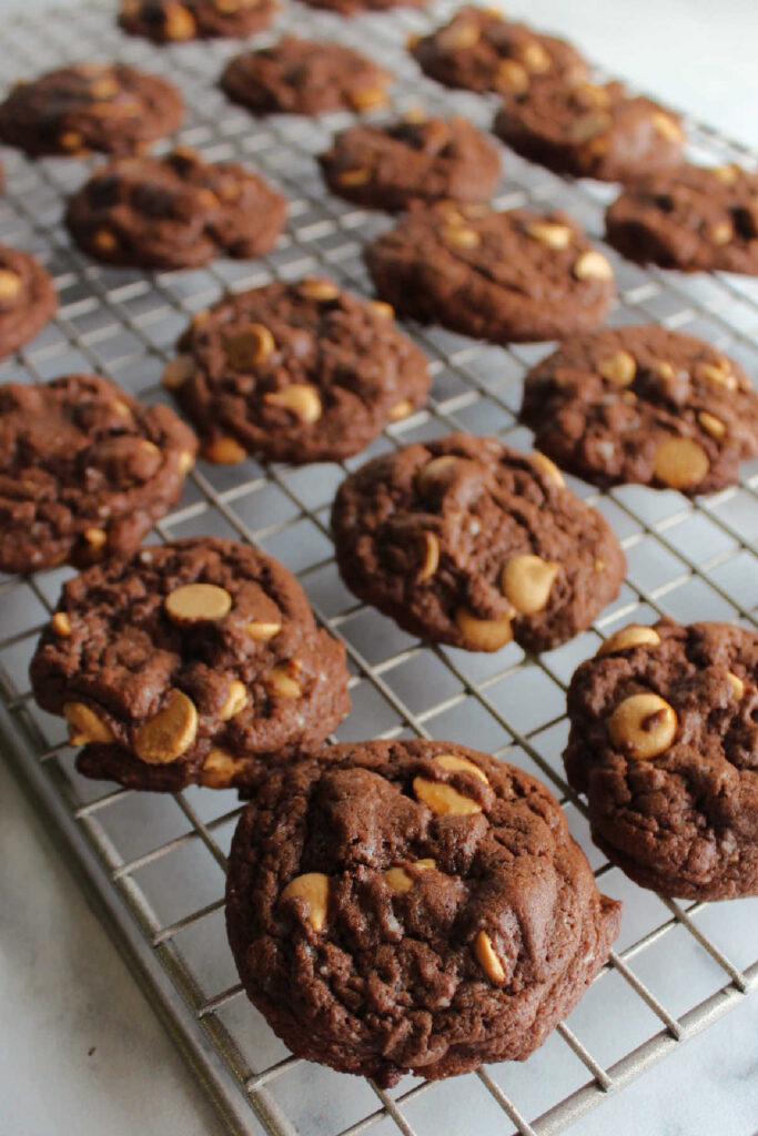 Freshly baked chocolate cake mix cookies with peanut butter chips on wire cooling rack.