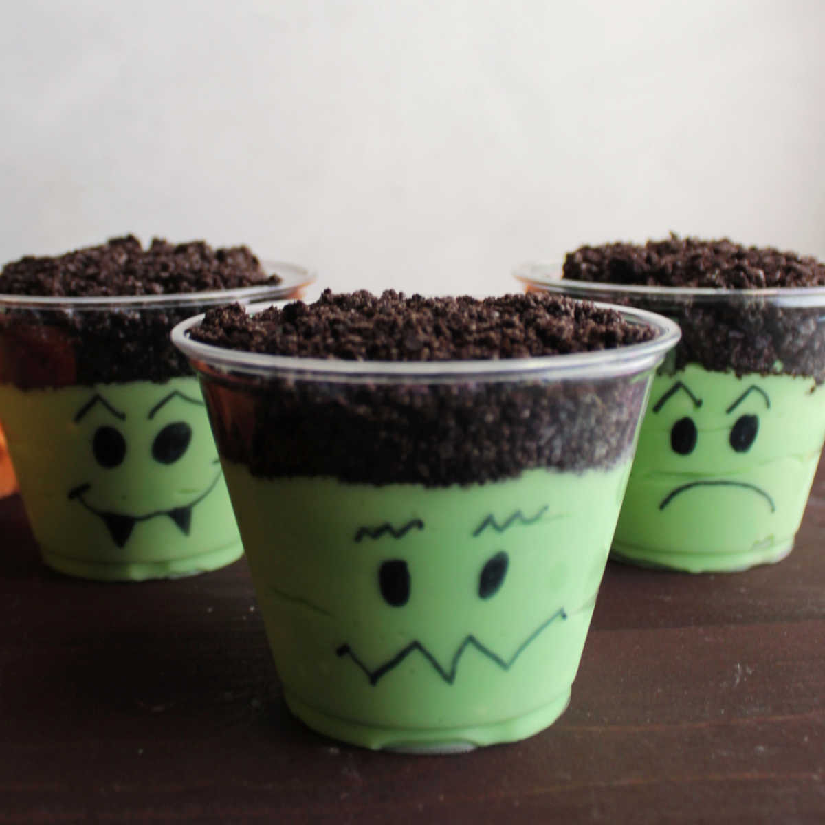 Three pudding cups with green pudding mixture and chocolate cookie crumb topping with faces drawn on them to look like Frankenstein.