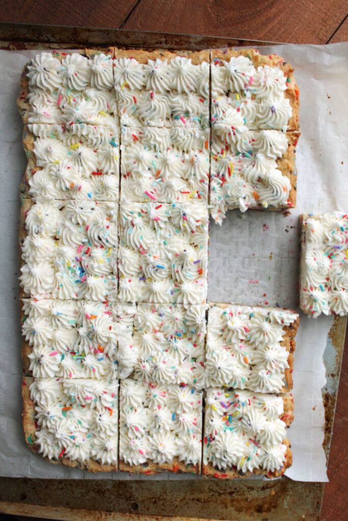 Piece pulled out from a big batch of soft sugar cookie bars with sprinkles.