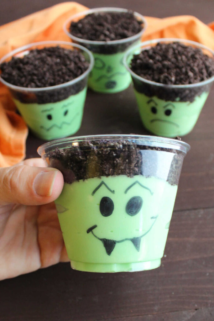Hand holding a dirt pudding cup with a vampire face drawn in front of where the green pudding mixture is and the oreo crumbs on top make the dark hair.