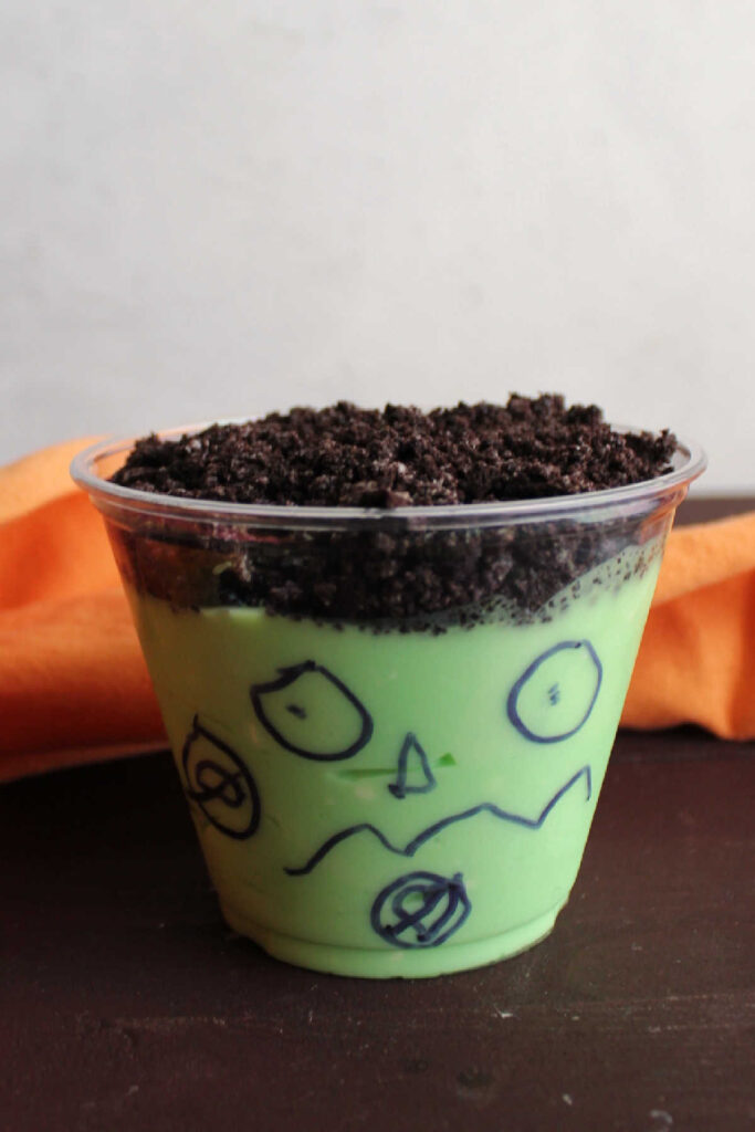 Green dirt pudding cup with a fun face drawn by a child on the cup.