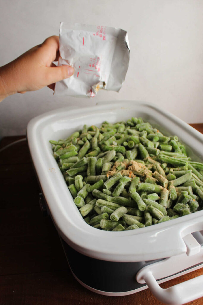 Child's hand sprinkling soup mix over slow cooker filled with frozen green beans.