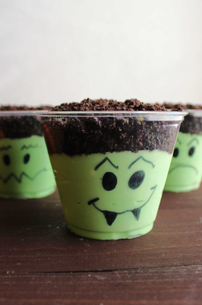 Green dirt pudding cups with Halloween faces drawn on them, ready to eat.